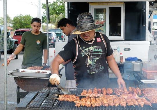 Iggi Nakashima, at front, grills chicken with Paul Yeban, left, and Shane Narian at the G&G's Barbecue food truck at the King of the Streets Food Truck Throwdown event at Skinner Plaza in Hagatna March 17, 2019.