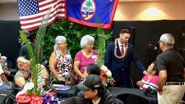 In this March 18, 2019 file photo, Del. Mike San Nicolas, D-Guam, talks with World War II survivors about war reparations and other issues of importance to them, during the delegate's first town hall at the newly opened district office.