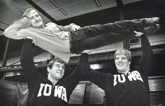 From 1982: Hawkeyes wrestlers Ed Banach, left, and Pete Bush lift Iowa coach Dan Gable.