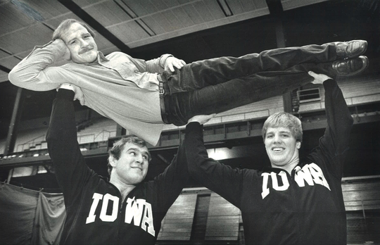 From 1982: Hawkeyes wrestlers Ed Banach, left, and Pete Bush lift Iowa coach Dan Gable.