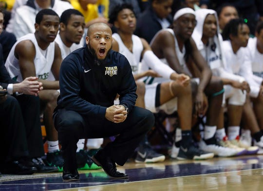 Crispus Attucks Tigers head coach Chris Hawkins calls out to his players in their IHSAA boys' Semi-State basketball game Saturday at Seymour. An Attucks player received a technical for striking another player in the game; Hawkins apologized privately and publicly.