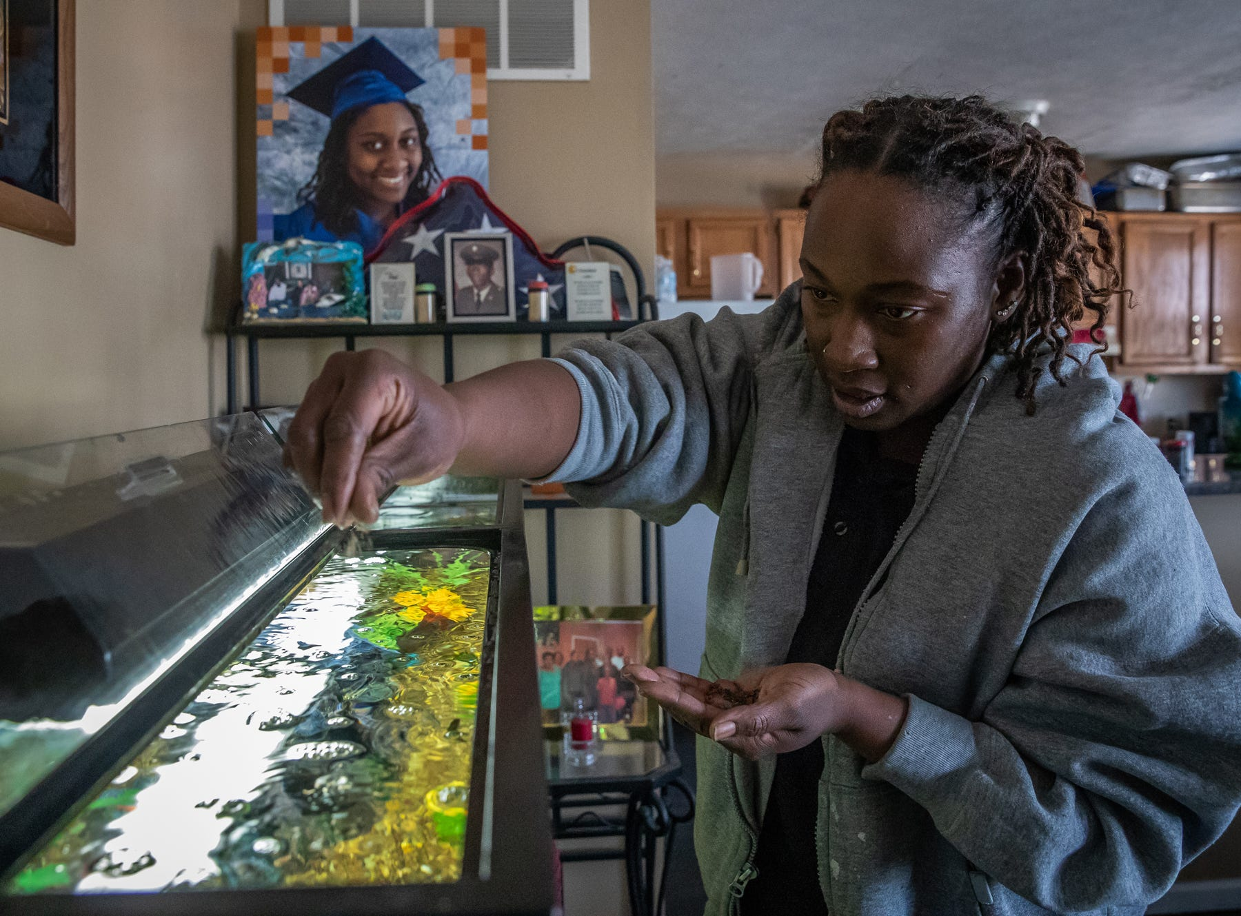 "Raniesia Gentillion feeds her family's fish inside her home on the east side of Indianapolis on Monday, March 18, 2019. The water heater the family had to purchase when renting a home, located at 1313 Eugene Street in Indianapolis, still sits on top aquarium. ""My dog's water bowl, the cats, they were solid,"" said Gentillion. ""We had to dish out another $80 to buy a heater for the fish tank."""