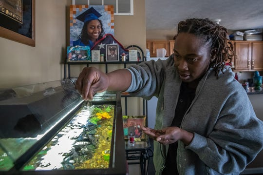 Raniesia Gentillion feeds her family's fish inside her home on the east side of Indianapolis on Monday, March 18, 2019. The water heater the family had to purchase when renting a home, located at 1313 Eugene Street in Indianapolis, still sits on top aquarium.