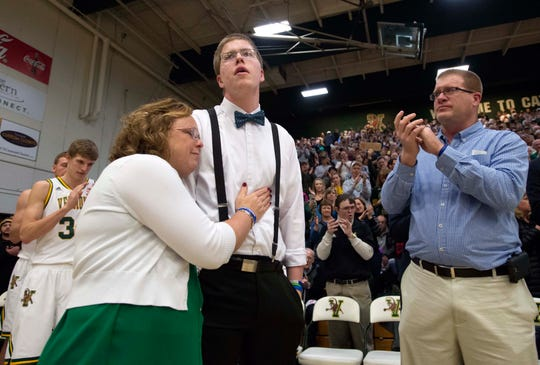 Josh Speidel gets a hug from his mother Lisa as his father Dave looks on as he is introduced before the start of the University of Vermont's game against Stony Brook's in Burlington on January 30, 2016.