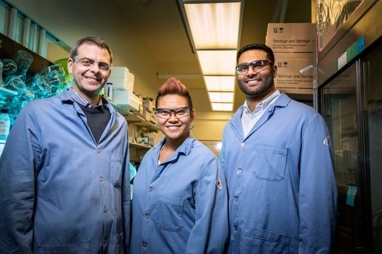 Chemistry professor Martin Burke, left, is joined by Katrina Muraglia, center, who just completed her PHD in biochemistry, and grad student Rajeev Chorghade, in the labs at Roger Adams Laboratory at the University of Illinois at Urbana-Champaign where they continue research on the mechanisms that control the processes that affect cystic fibrosis.