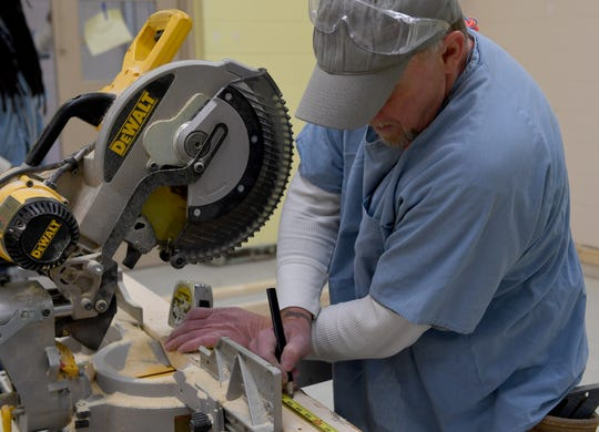 TDOC inmate Rodney Kirby measures a 2x4 to cut on the floor inside of West Tennessee Regional Training Center as for new mock jail cells. Kirby is a part of the National Center for Construction Education and Research certification program.