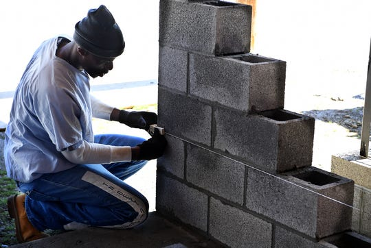 TDOC inmate Michael Willis sets a level for a concrete wall being built outside of the West Tennessee Regional Training Center and Madison County Sheriff's Office, Monday, March 18. Willis is a part of the National Center for Construction Education and Research certification program.