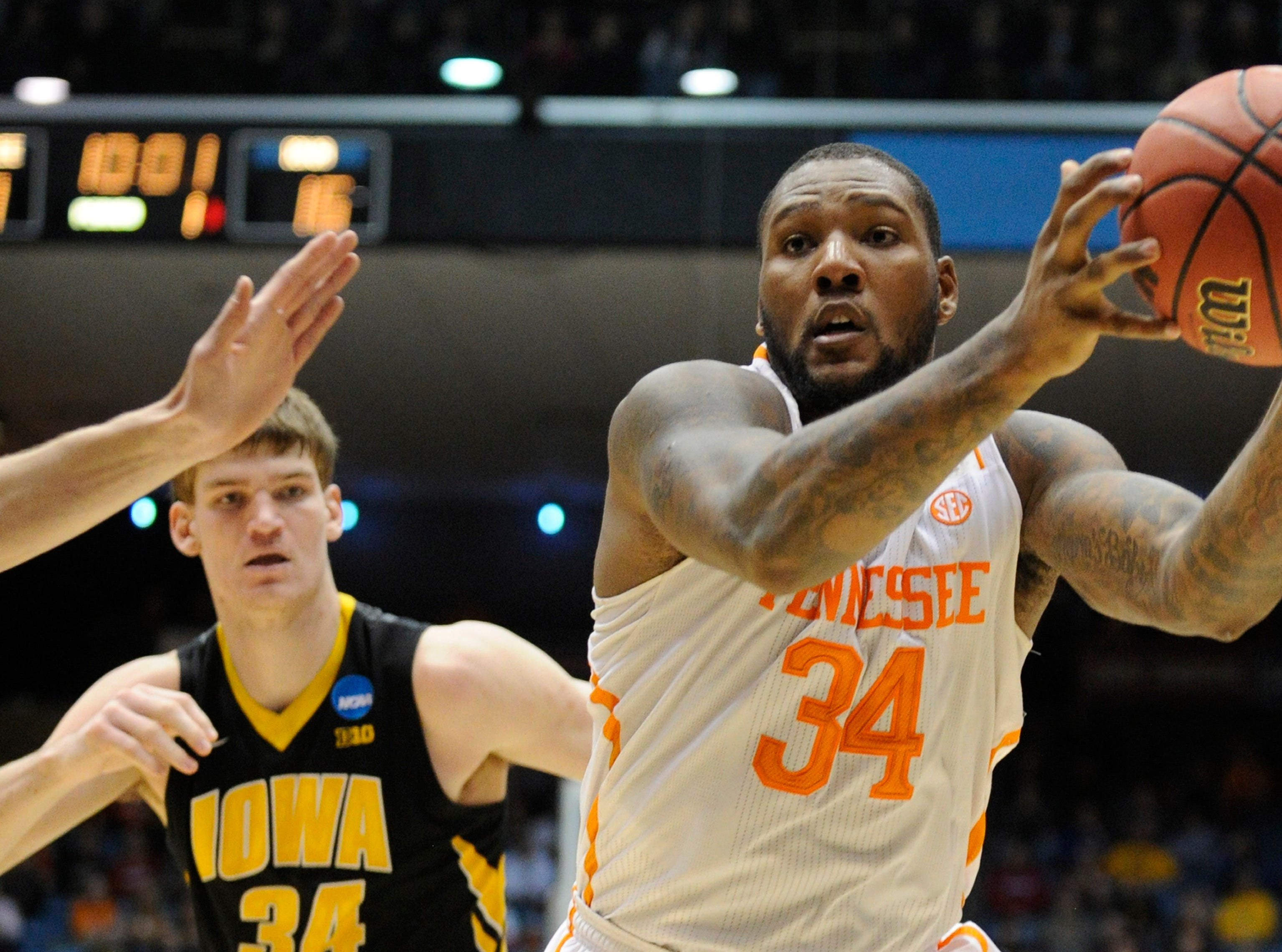 Tennessee forward Jeronne Maymon (34), right, reaches for a pass as Iowa center Adam Woodbury (34), left, defends during the first half of an NCAA tournament First Four play-in game at the University of Dayton Arena in Dayton, Ohio on Wednesday, March 19, 2014.