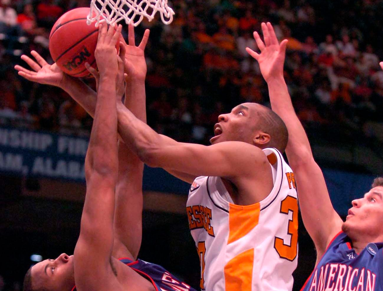 Tennessee's J.P. Prince takes a shot tangled up with American University's Romone Penny and Frank Borden during first round competition of the 2008 NCAA Tournament in Birmingham on Friday. Tennessee won the game 72-57 and advance to play the winner of Butler vs. South Alabama.