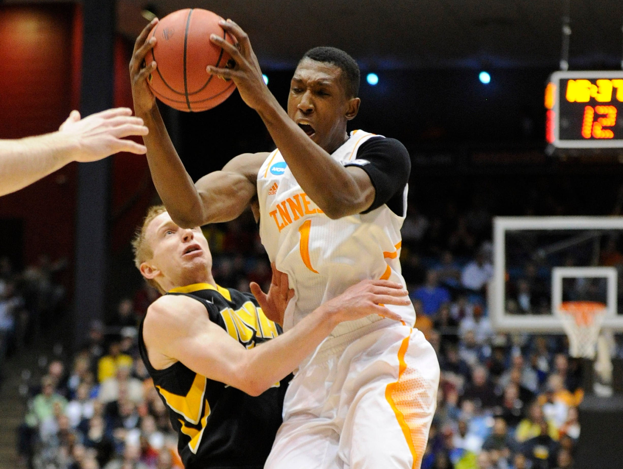 Iowa guard Mike Gesell (10) grabs Tennessee guard Josh Richardson (1) during the first half of an NCAA tournament First Four play-in game at the University of Dayton Arena in Dayton, Ohio on Wednesday, March 19, 2014.