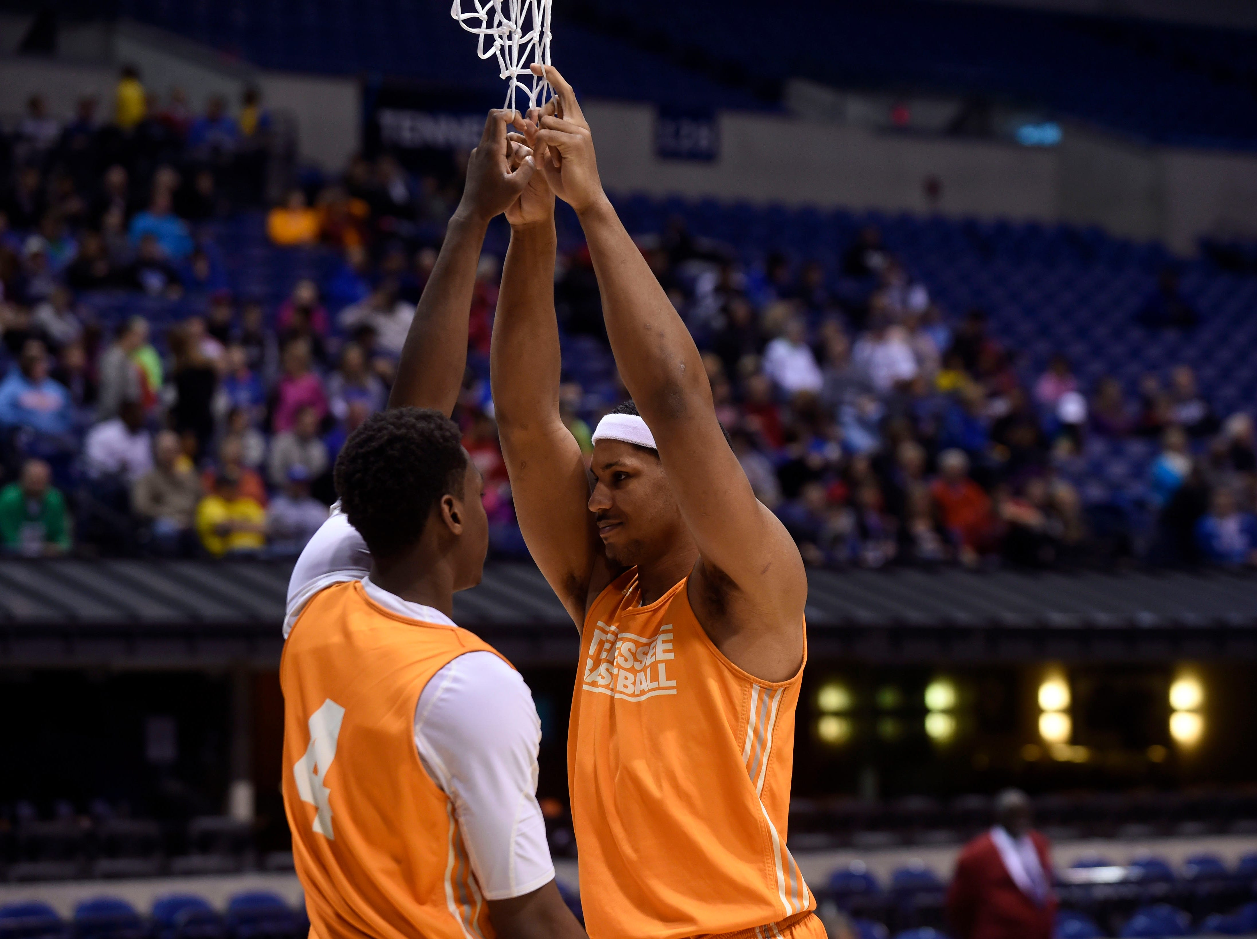Tennessee guard Armani Moore, left, and Tennessee forward Jarnell Stokes use the basketball net to stretch during practice before Tennessee's NCAA Sweet Sixteen game against Michigan at Lucas Oil Stadium in Indianapolis, IN on Thursday, March 27, 2014.