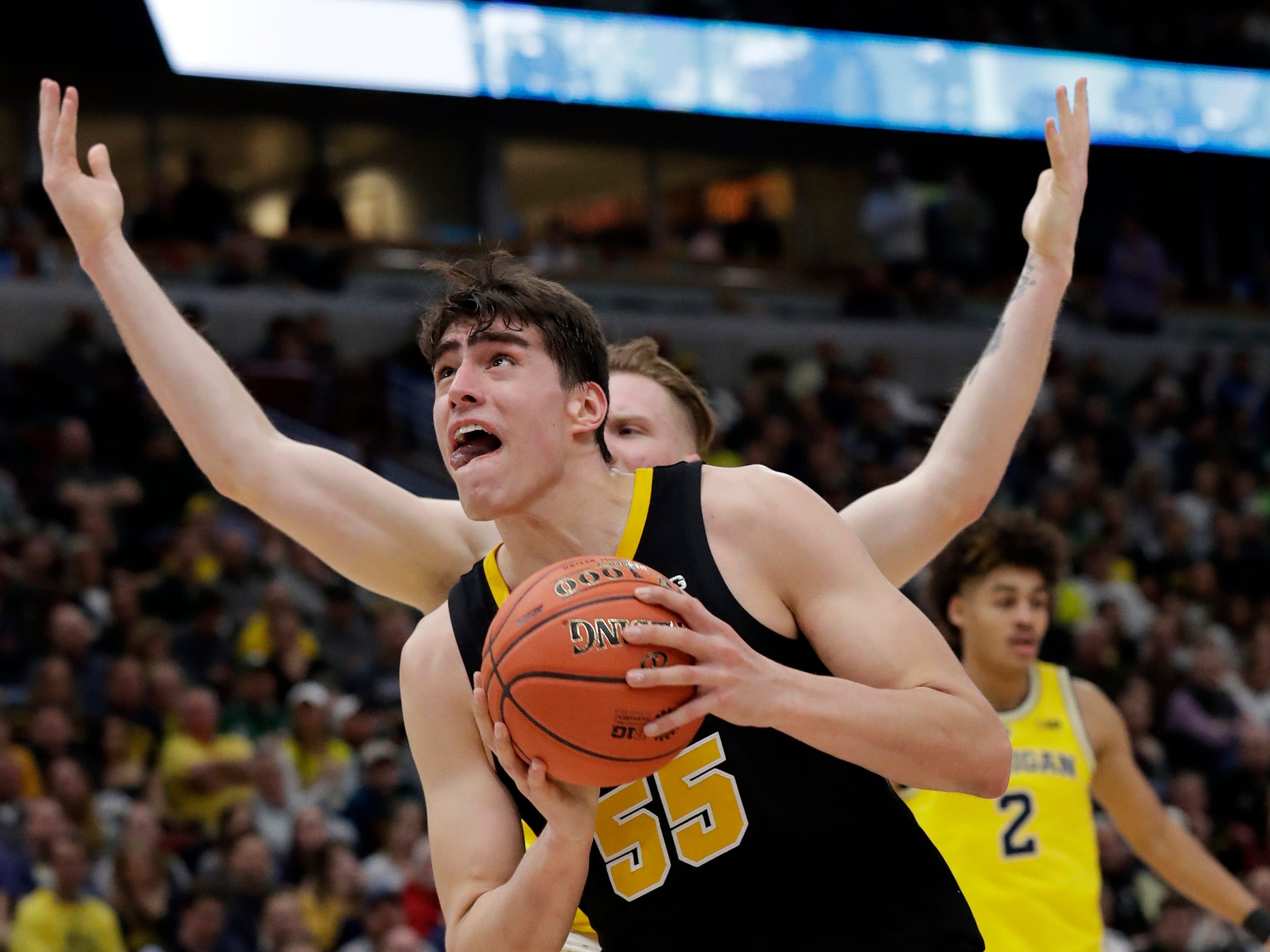 Iowa's Luka Garza (55) drives against Michigan's Ignas Brazdeikis during the first half of an NCAA college basketball game in the quarterfinals of the Big Ten Conference tournament, Friday, March 15, 2019, in Chicago.