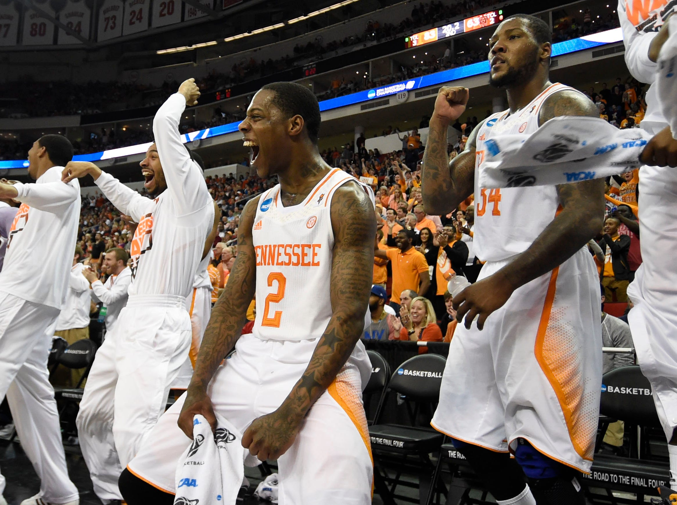 Tennessee guard Antonio Barton (2), center, and Tennessee forward Jeronne Maymon (34), right, celebrate with teammates after Tennessee secures a Sweet Sixteen berth by defeating Mercer 83-63 in a third-round NCAA tournament game at the PNC Arena in Raleigh, N.C. on Sunday, March 23, 2014.
