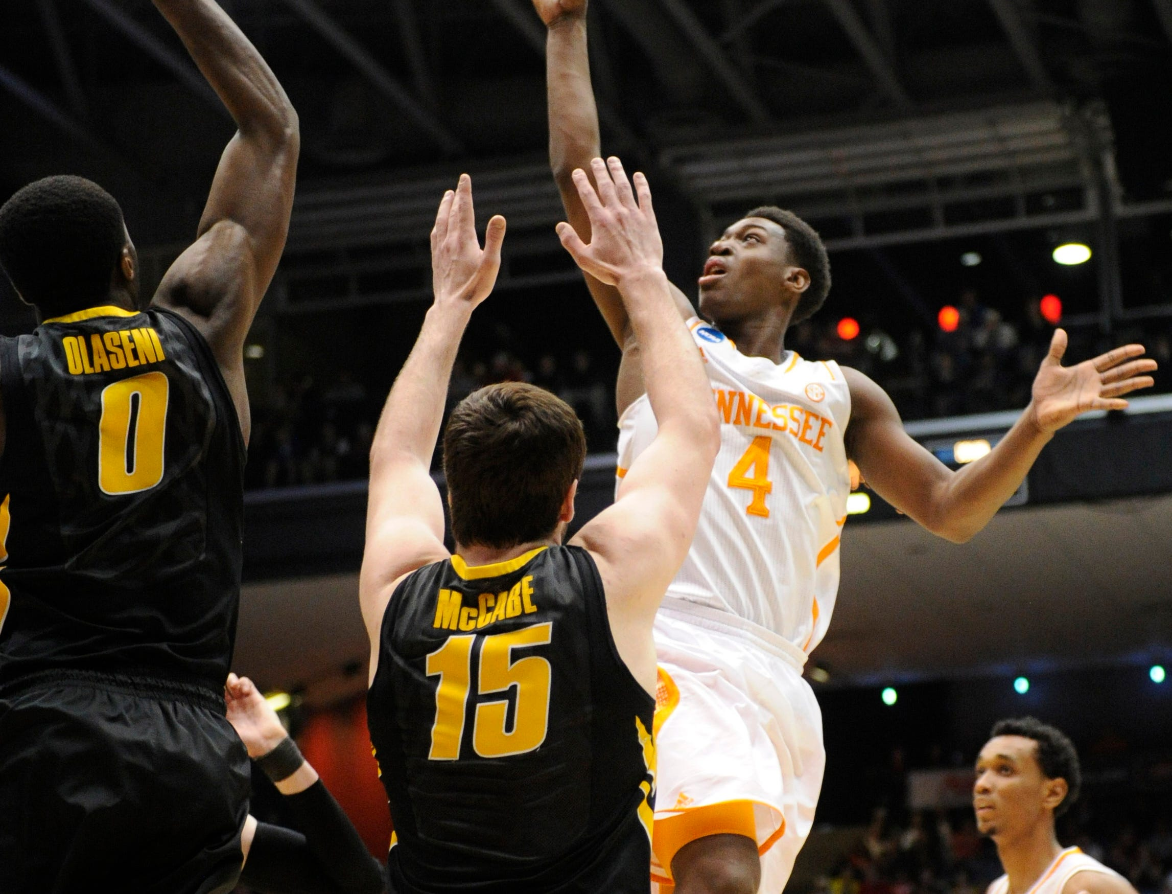 Tennessee guard Armani Moore (4) attempts a jumper against Iowa center Gabriel Olaseni (0) and Iowa forward Zach McCabe (15) during the first half of an NCAA tournament First Four play-in game at the University of Dayton Arena in Dayton, Ohio on Wednesday, March 19, 2014.