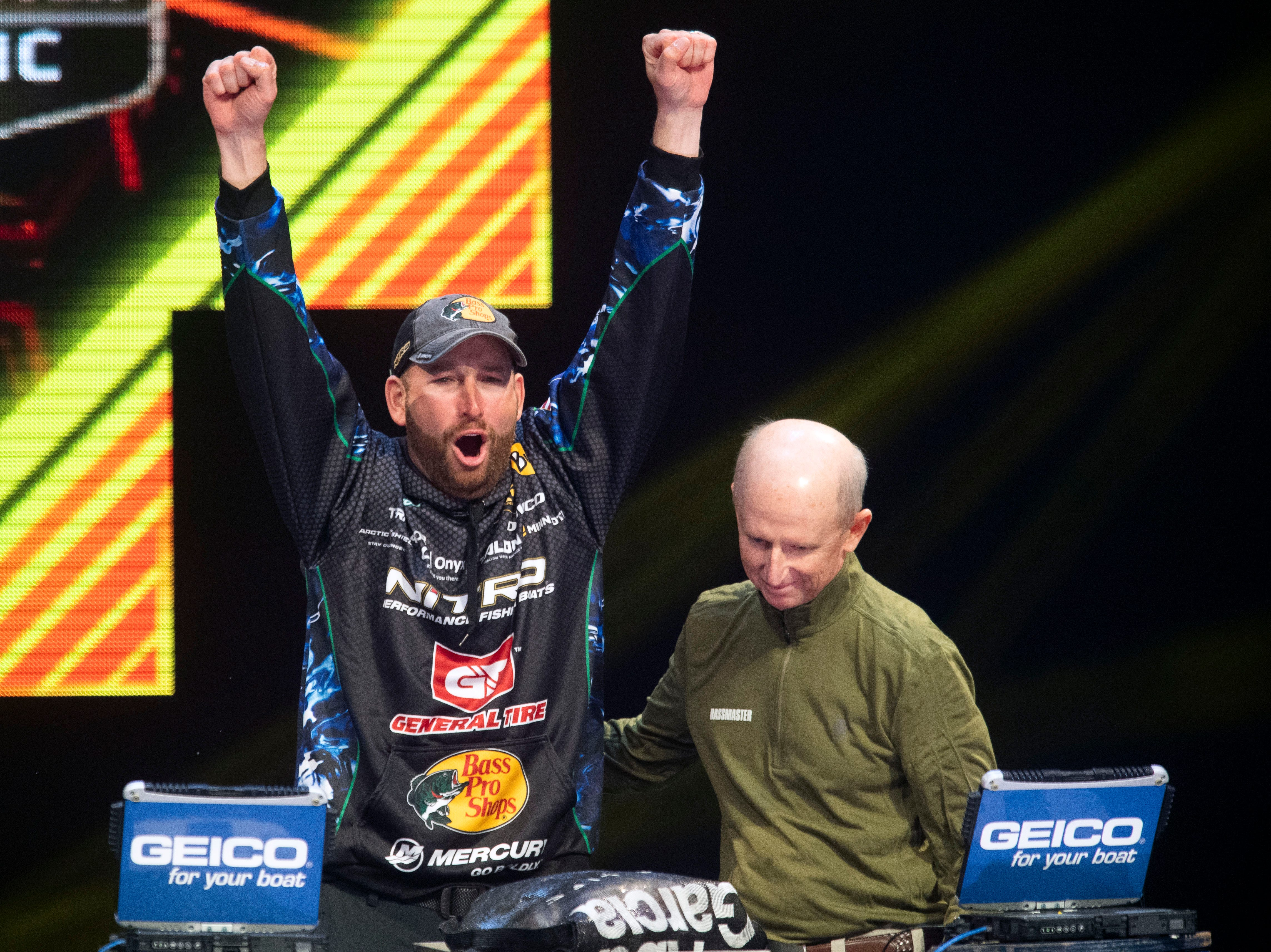 Ott DeFoe celebrates as his weigh-in gives him the lead in  the Bassmaster Classic during on Sunday, March 17, 2019. At right is tournament director Tripp Weldon.