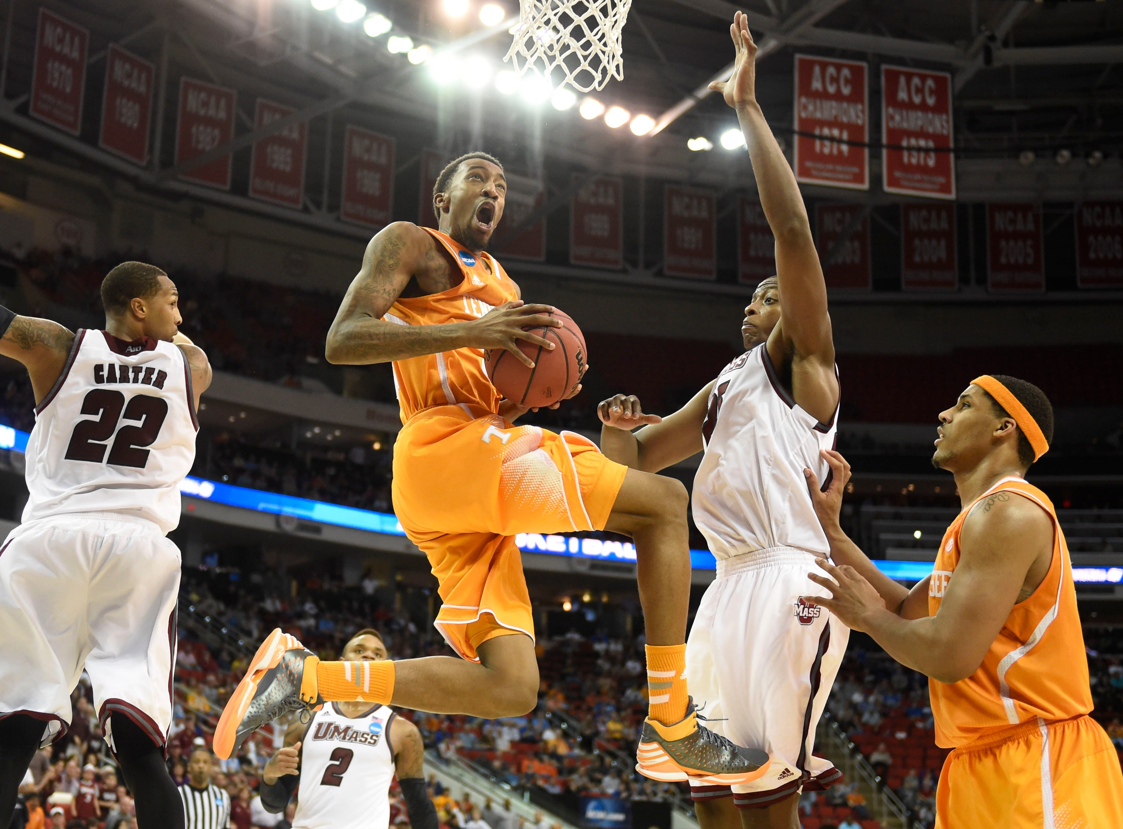 Tennessee guard Jordan McRae (52), center, gets to the hoop in between Massachusetts forward Sampson Carter (22) and Massachusetts center Cady Lalanne (25), while Tennessee forward Jarnell Stokes, right, looks on during the second half of an NCAA tournament game at the PNC Arena in Raleigh, N.C. on Friday, March 21, 2014. Tennessee won 86-67.