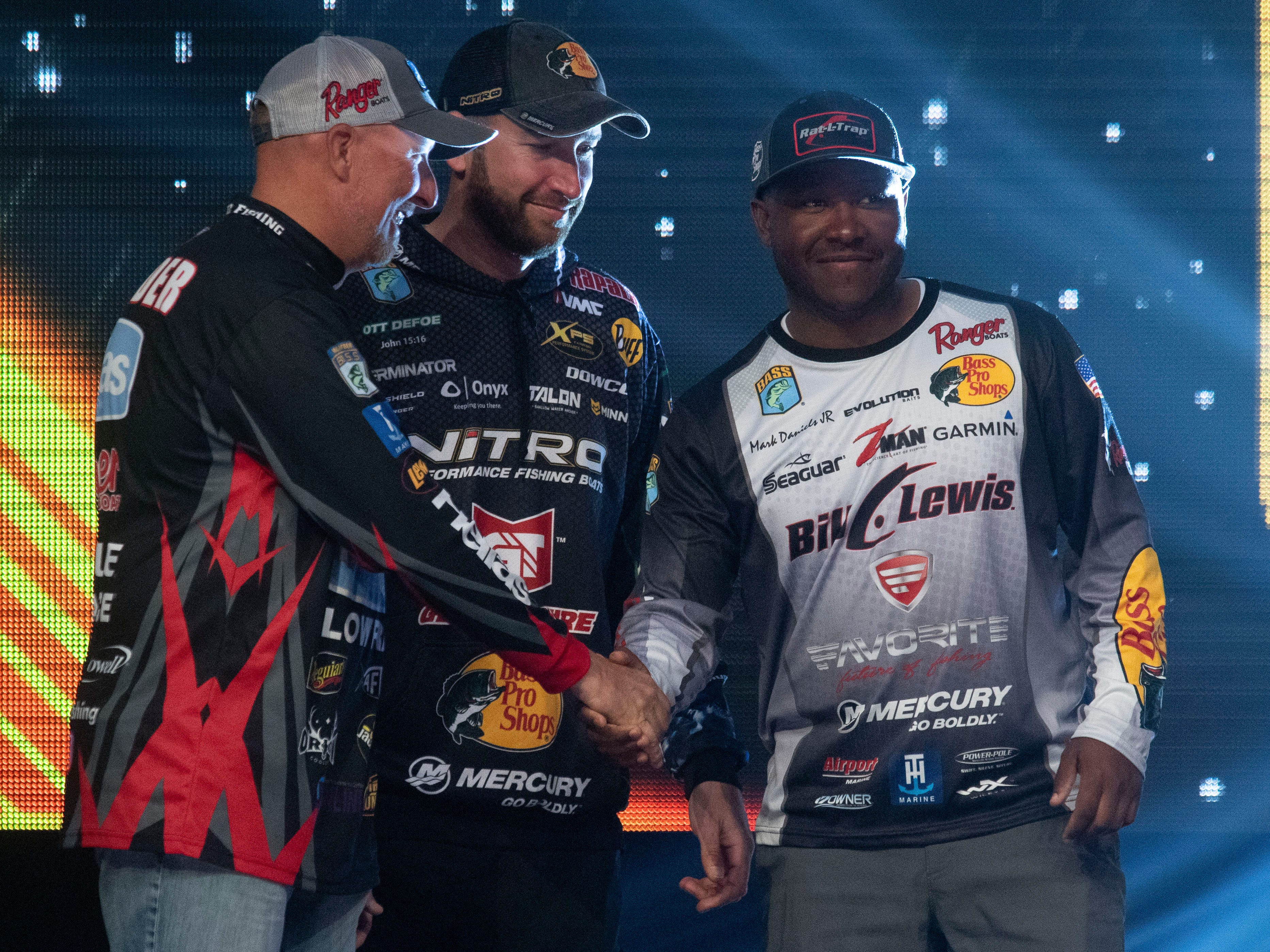 Spring City, TN resident Wesley Strader, left, and Knoxville native Ott DeFoe greet fellow angler Mark Daniels Jr. on stage as three of the six finalist in the weigh-in on the final day of the Bassmaster Classic at Thompson-Boling Arena on Sunday, March 17, 2019.