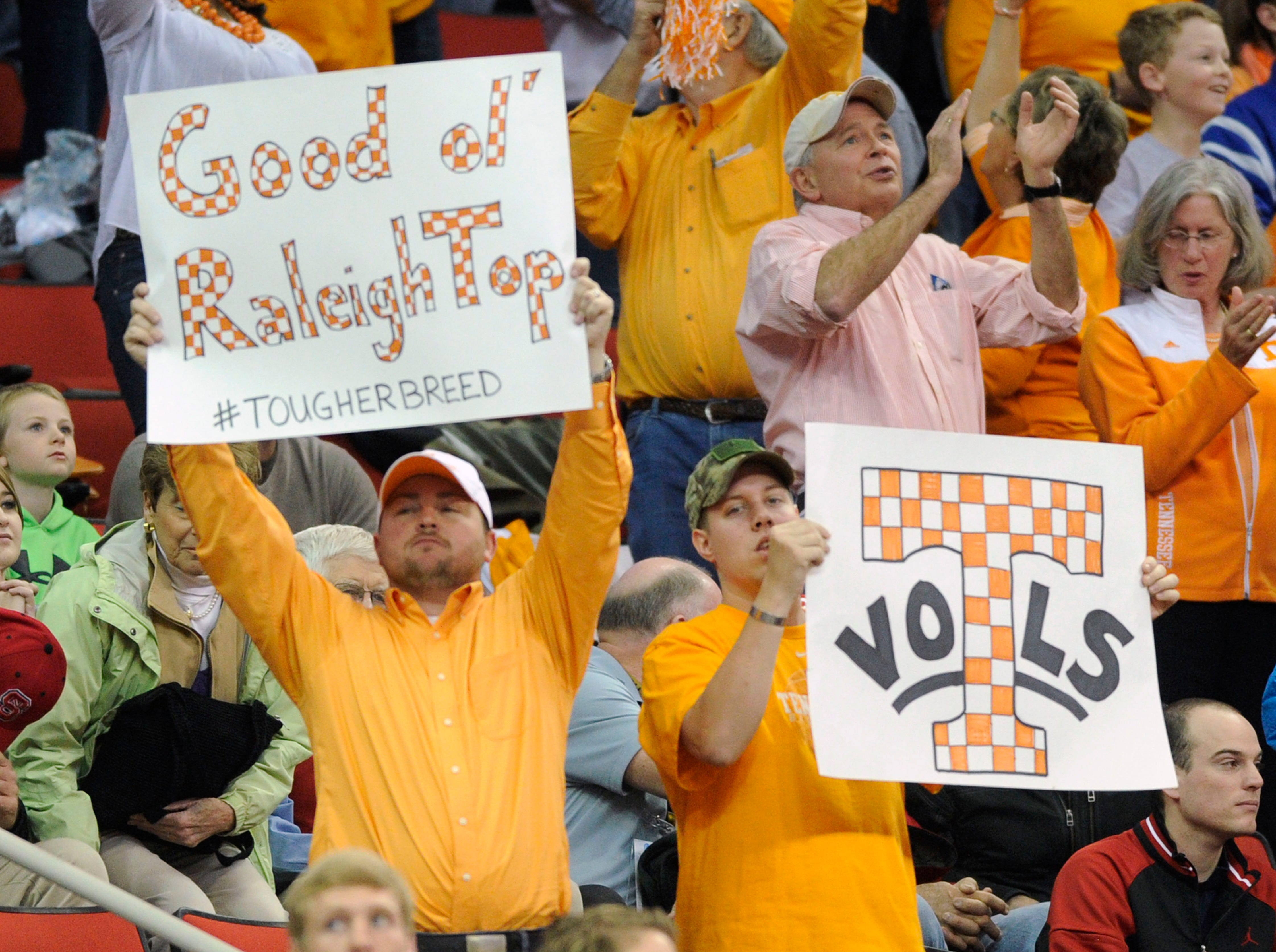 Tennessee fans hold up signs during the first half of a third-round NCAA tournament game against Mercer at the PNC Arena in Raleigh, N.C. on Sunday, March 23, 2014.