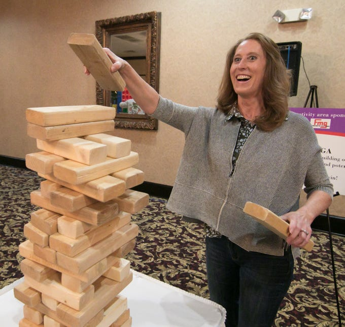 Lisa Miles plays a variant of Jenga, racing against another to build a tower faster than their opponent without it falling down. The game was one of several to raise money at the Love, INC benefit comedy night held at Crystal Gardens Thursday, March 14, 2019.