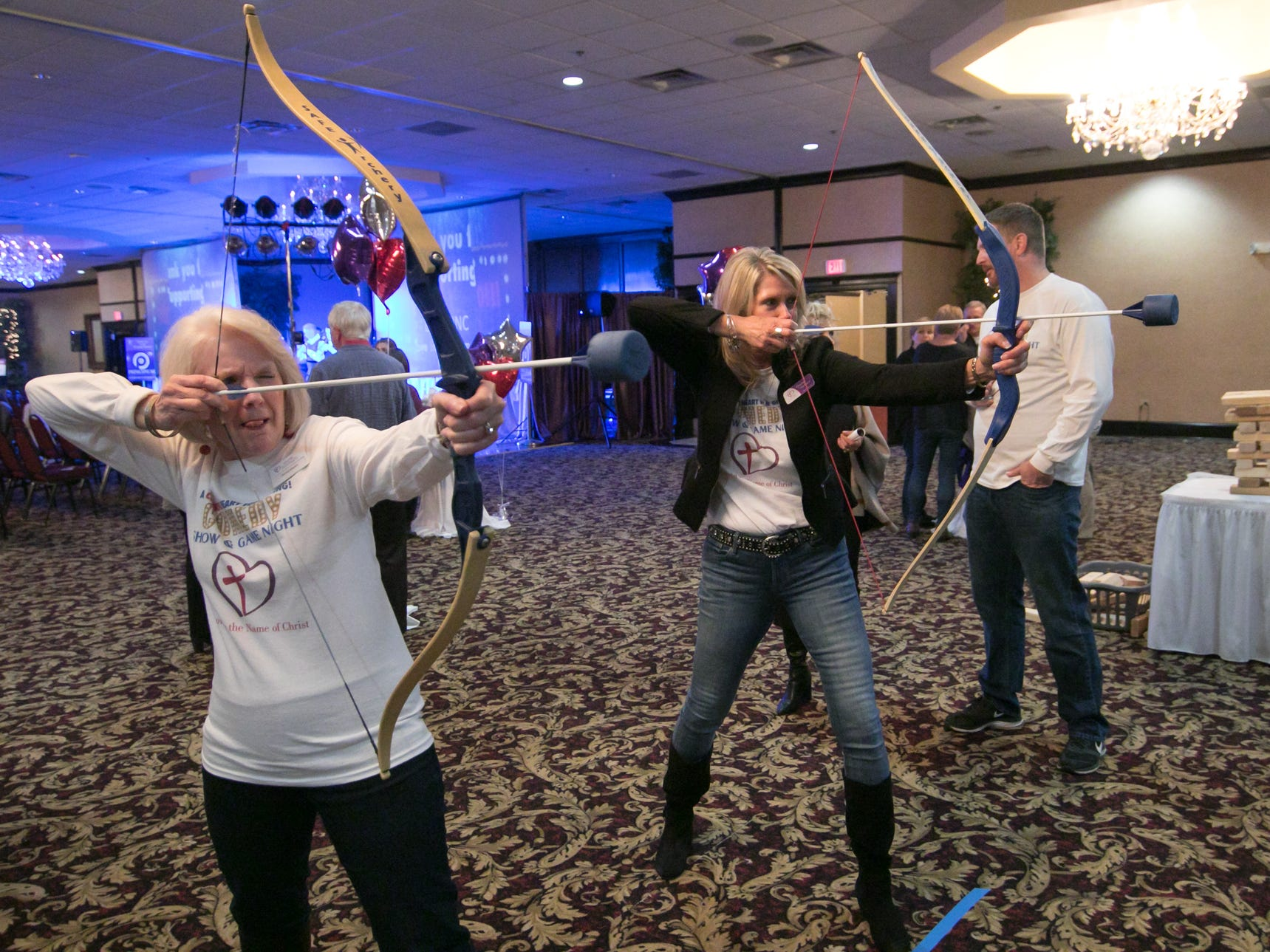 At left, Donna Alberta, development coordinator for Love, INC, and Queta Siefker, member of Love INC's board of directors, line up their shots in a archery hoverball game, part of the fundraising festivities of the organization's comedy night event Thursday, March 14, 2019.