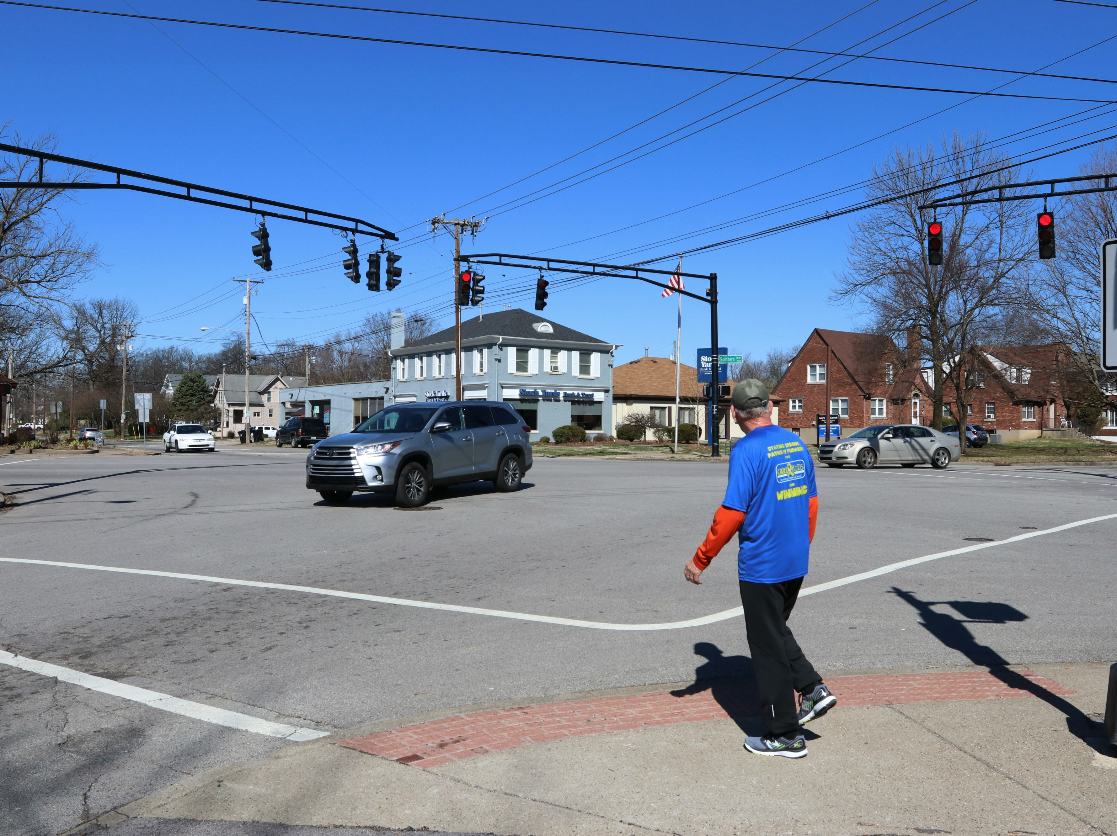 A jogger crosses Southern Parkway at a highly used five-way intersection in Louisville's Beechmont neighborhood. 3/16/19