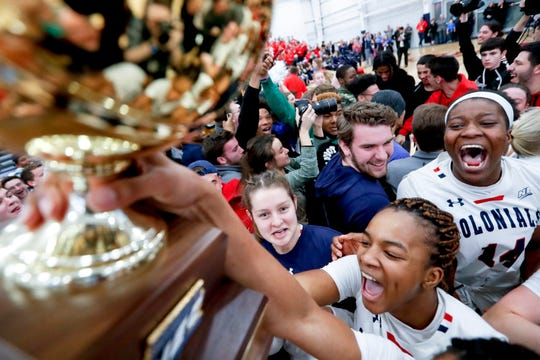 Robert Morris' Nneka Ezeigbo, center, holds the trophy as she celebrates after defeating St. Francis for the championship of the Northeast Conference women's tournament, Sunday, March 17, 2019.