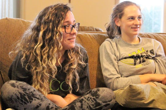Brazilian high school student Luiza Vessoni sits with her host family Thursday evening. She is currently attending Harding High School as part of a year-long exchange program.
