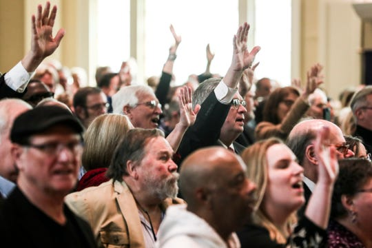 March 18, 2019 - Friends and family raise their hands and sing along to music during a memorial service for John Kilzer at St. John's United Methodist Church.