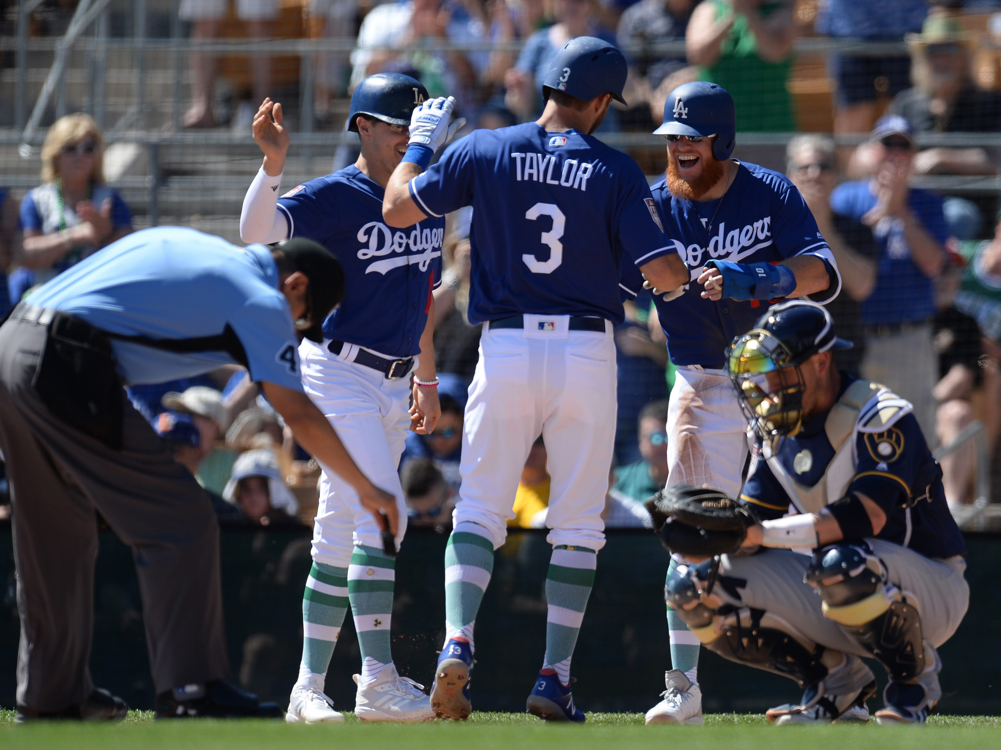 Chris Taylor of the Dodgers is greeted teammates Enrique Hernandez (left) and Justin Turner after he belted a three-run homer off Brewers starter Zack Davies in the first inning.