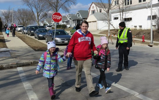 Crystal Kekipi of West Allis crosses the street near Woodrow Wilson Elementary School in West Allis with her daughters Alyssa (left) and Emma on Monday, March 18. West Allis Police Officer Darrin Kmichik (at right), was one of many police officers pressed into crossing guard duty after a former crossing guard provider abruptly closed. Wauwatosa announced a new crossing guard company has been hired for the 2019/2020 school year.