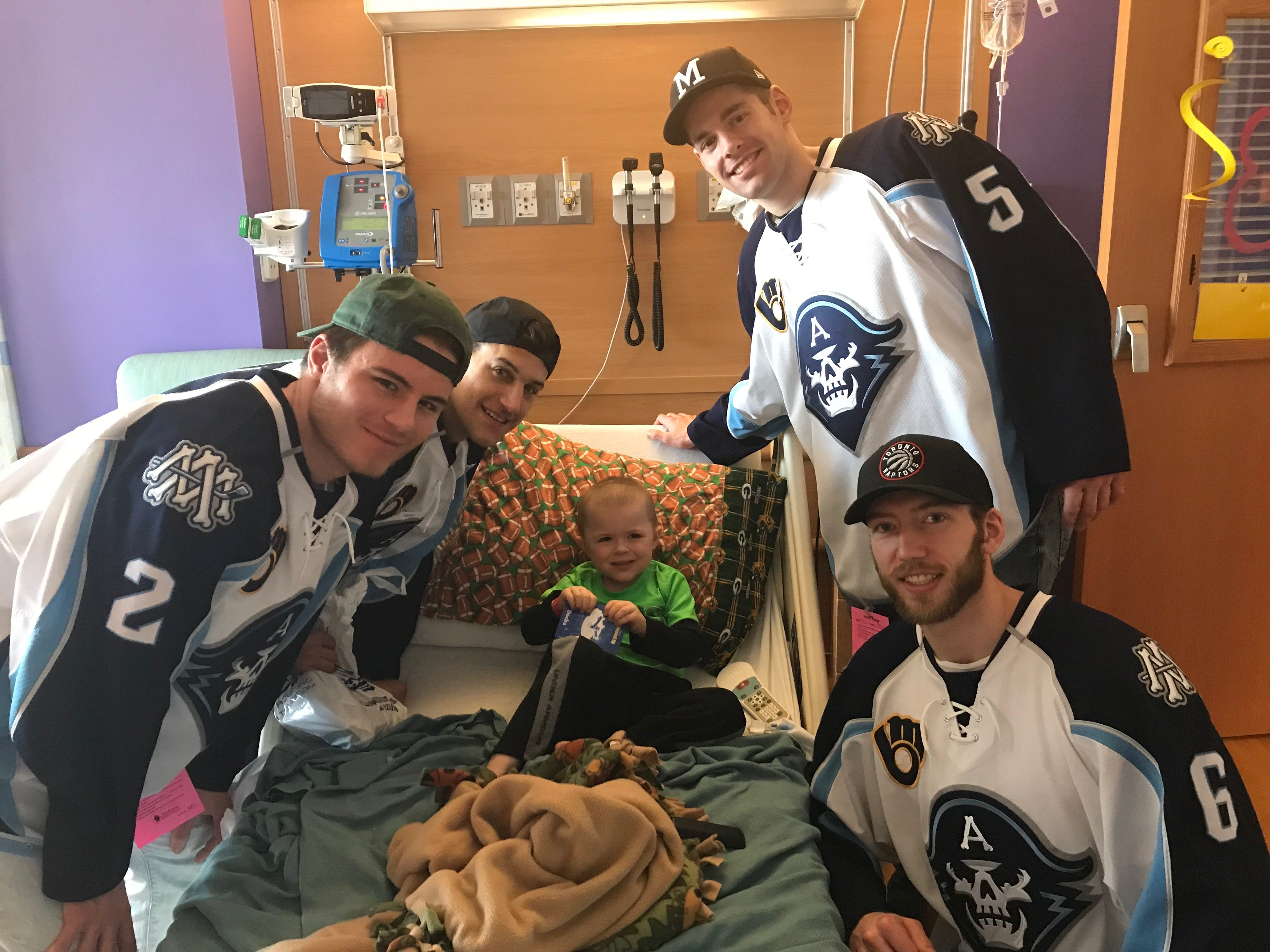 Some members of the Milwaukee Admirals visit Lincoln Maziasz during his leukemia treatment.