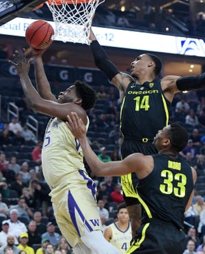 Oregon's Kenny Wooten (14) and Francis Okoro converge on Washington's Noah Dickerson in the Pacific-12 championship game. The Ducks'  defense has been stellar during an eight-game winning streak.