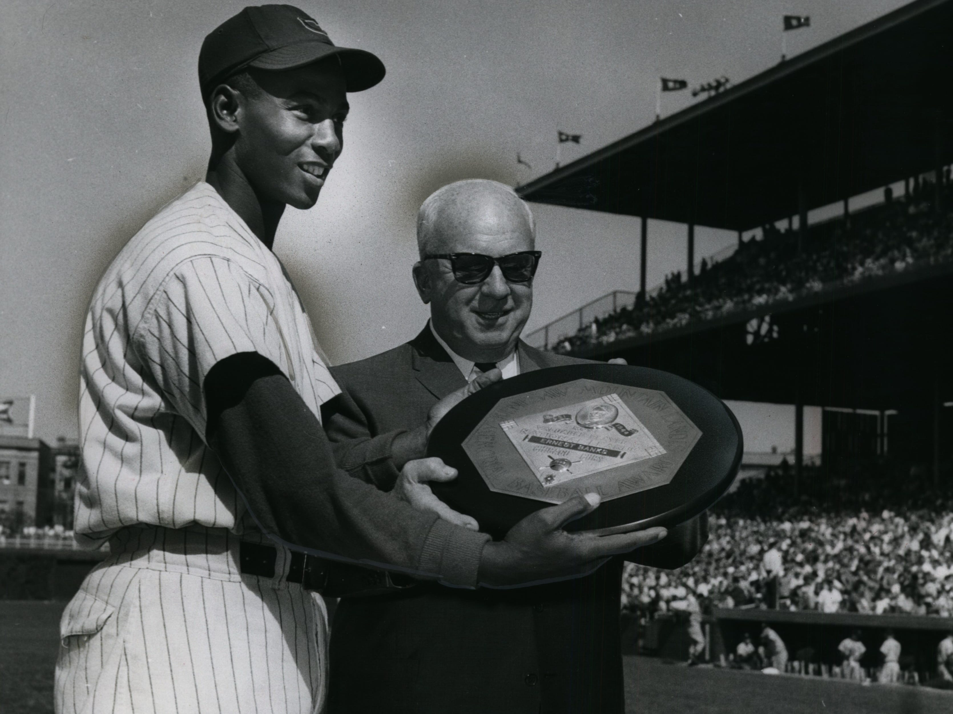 Chicago Cubs star Ernie Banks receives the plaque for being named the 1959 National League Most Valuable Player from NL President Warren Giles at Wrigley Field on May 16, 1960. Banks was the first player in NL history to win the MVP two years in a row.