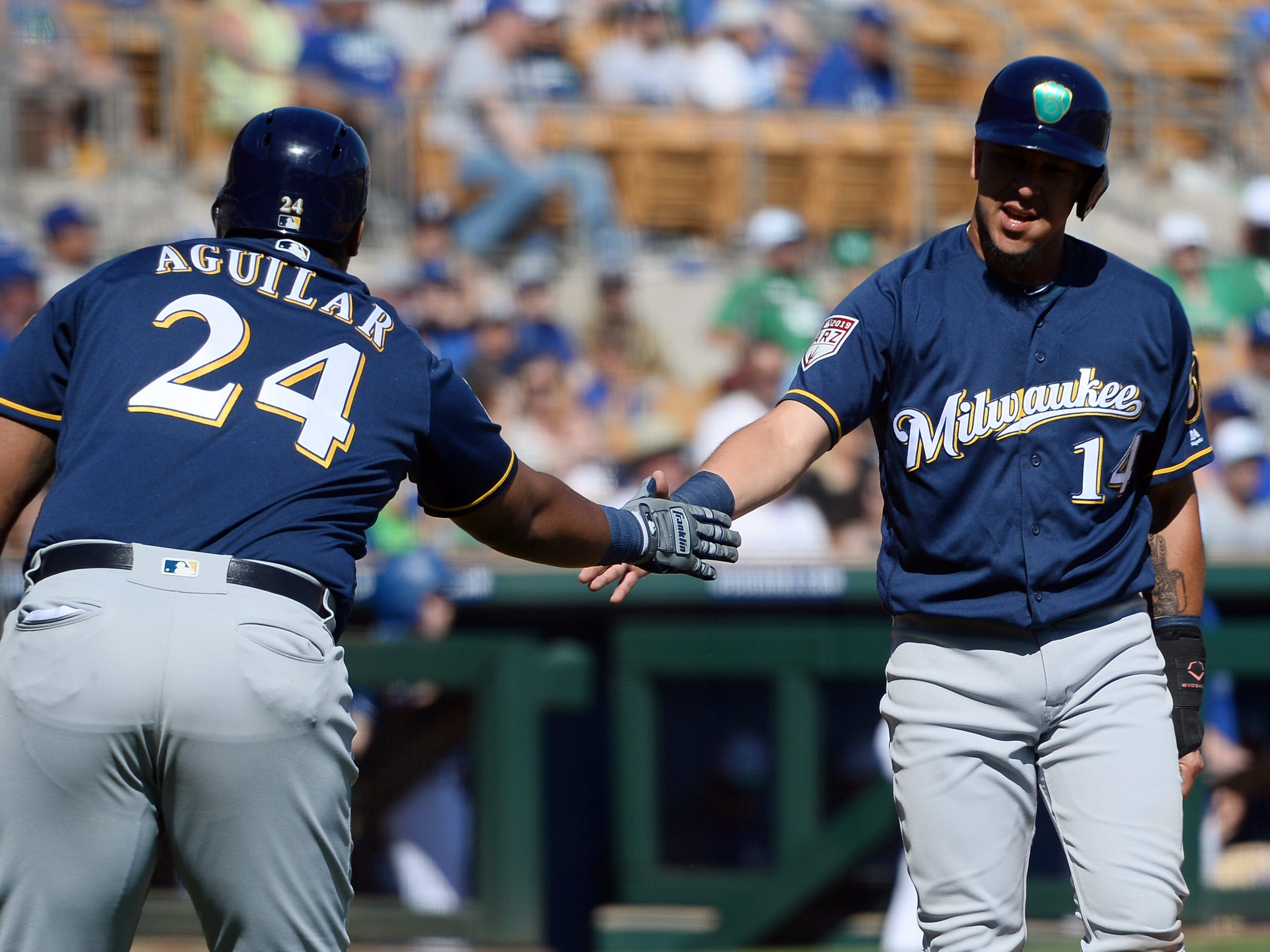 Hernan Perez is congratulated by Jesus Aguilar after scoring for the Brewers in the top of the fifth inning against the Dodgers.