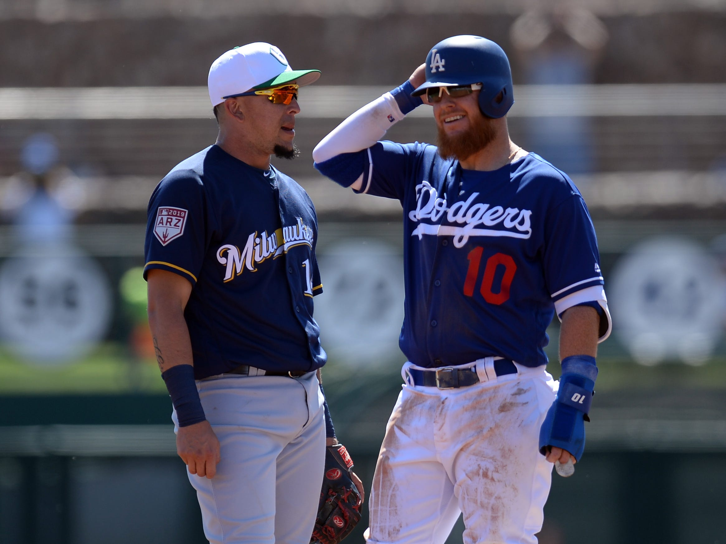 Brewers third baseman Hernan Perez and Dodgers third baseman Justin Turner talk during a small break in the action during the bottom of the first inning.