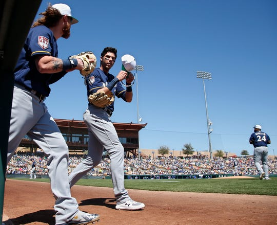 Christian Yelich (right) and Ben Gamel of the Brewers head out to the outfield for the bottom of the first inning against the Dodgers on Sunday afternoon at Camelback Ranch in Glendale, Ariz.