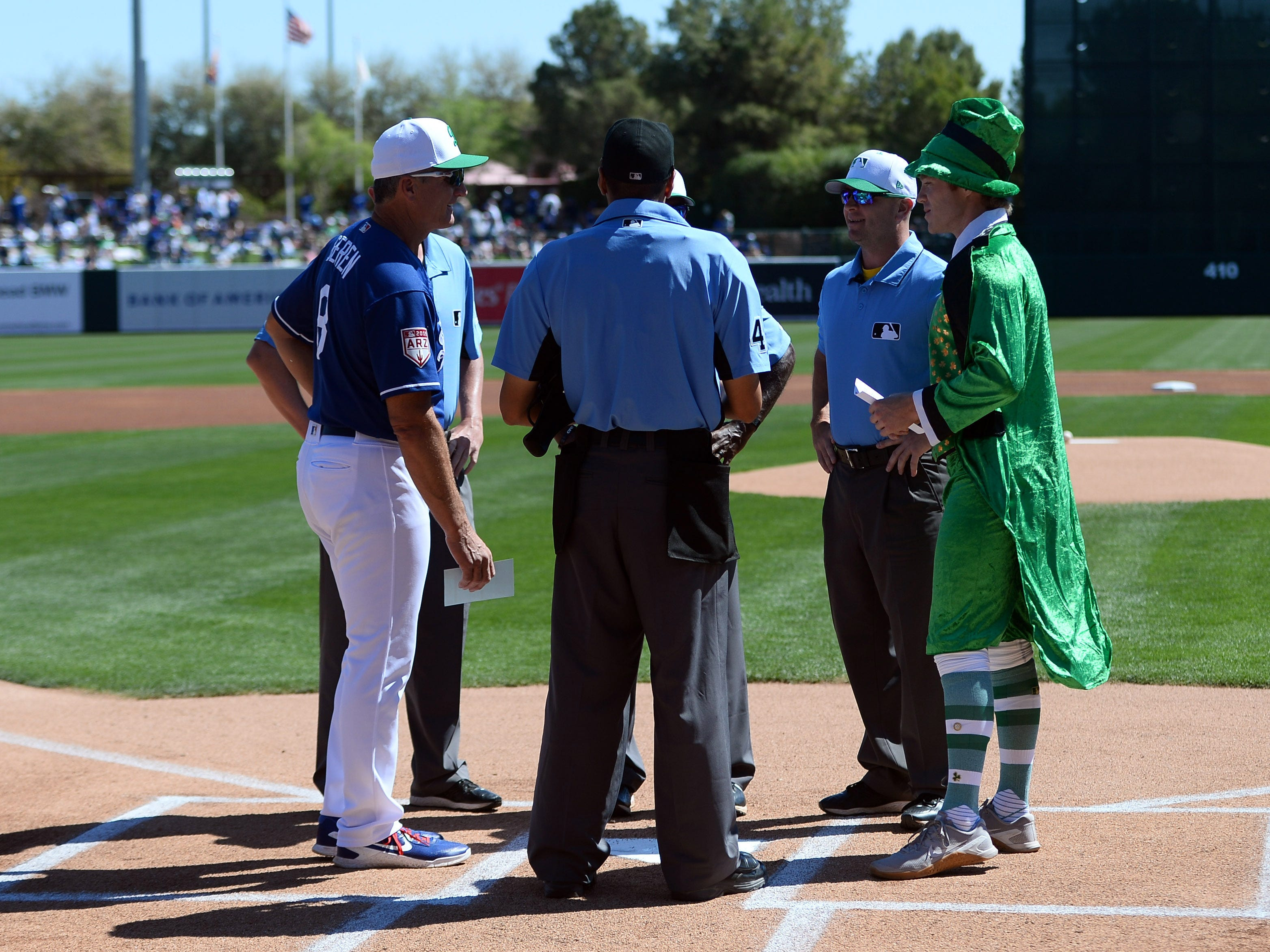 Brewers strength and conditioning intern Johnny Davis brings the team's lineup card to home dressed in a leprechaun outfit before the game against the Dodgers on Sunday.