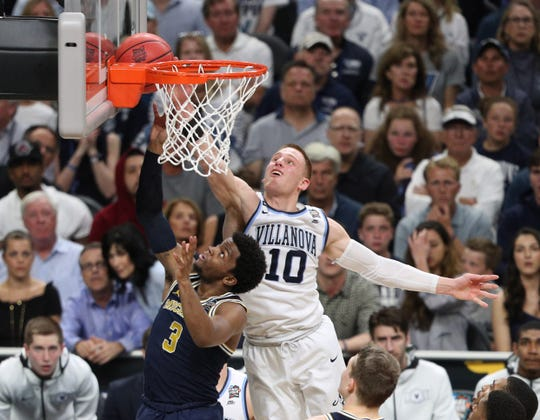 Villanova guard Donte DiVincenzo blocks a shot by Michigan's Zavier Simpson in the 2018 NCAA men's championship game.