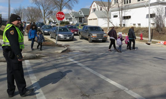West Allis Police Officer Darrin Kmichik helped children cross the street on March 18 in West Allis after a former crossing guard provider abruptly closed. Wauwatosa announced a new crossing guard company has been hired for the 2019/2020 school year.