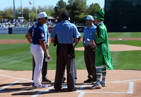Dodgers bench coach Bob Geren (left) and Brewers strength and conditioning intern Johnny Davis exchange lineup cards prior to the game Sunday.