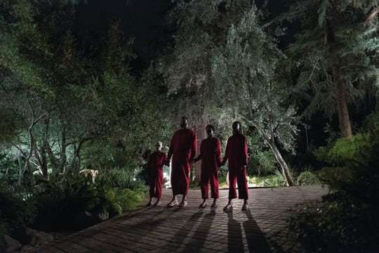 """The Wilson family doppelgängers (from left), Pluto (Evan Alex), Abraham (Winston Duke), Umbrae (Shahadi Wright Jospeh) and Red (Lupita Nyong'o) make their presence known in """"Us,"""" written, produced and directed by Jordan Peele."""