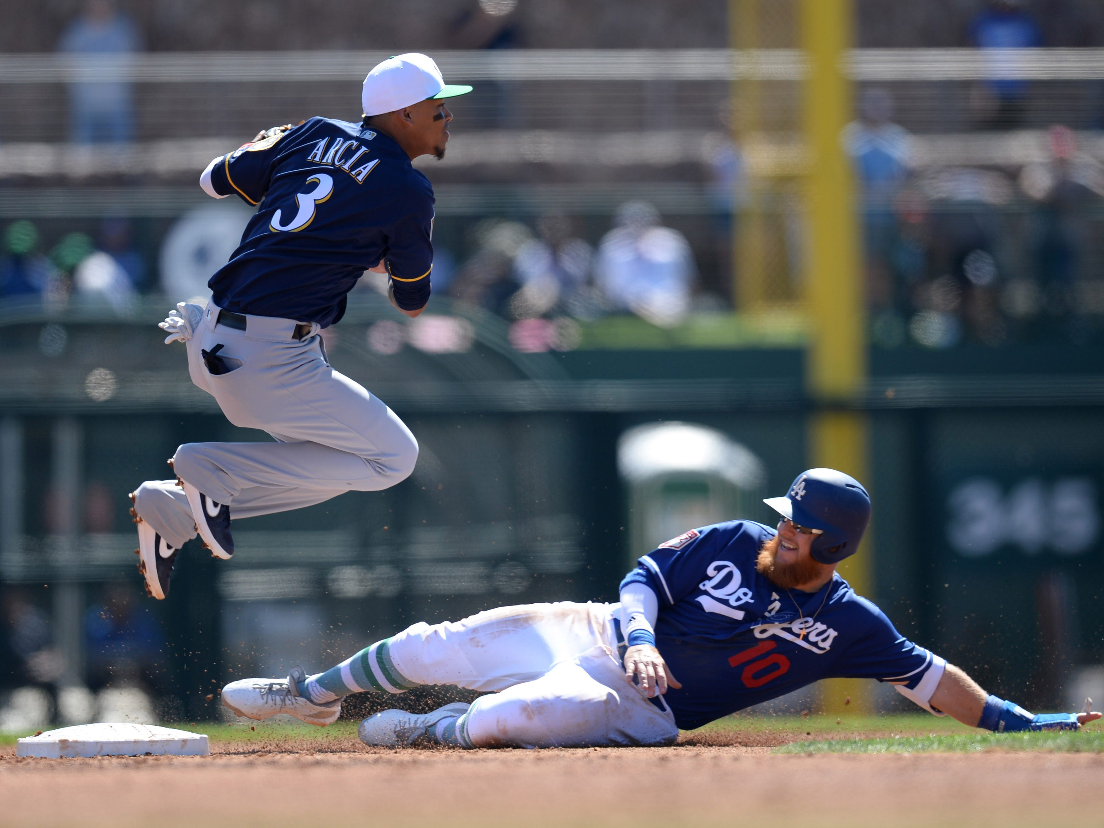 After throwing to first to complete a double play, Brewers shortstop Orlando Arcia  jumps to avoid a sliding Justin Turner of the Dodgers in the second inning.