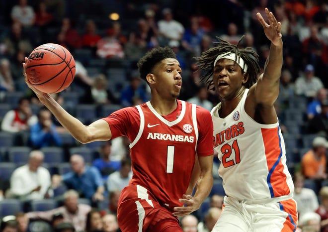 Arkansas guard Isaiah Joe (1) passes around Florida forward Dontay Bassett (21) in the first half of an SEC tournament game on March 14 in Nashville, Tenn.