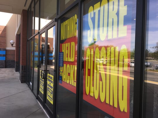 Signs on the Pier 1 Imports in the Shoppes at EastChase advertise a going-out-of-business sale.