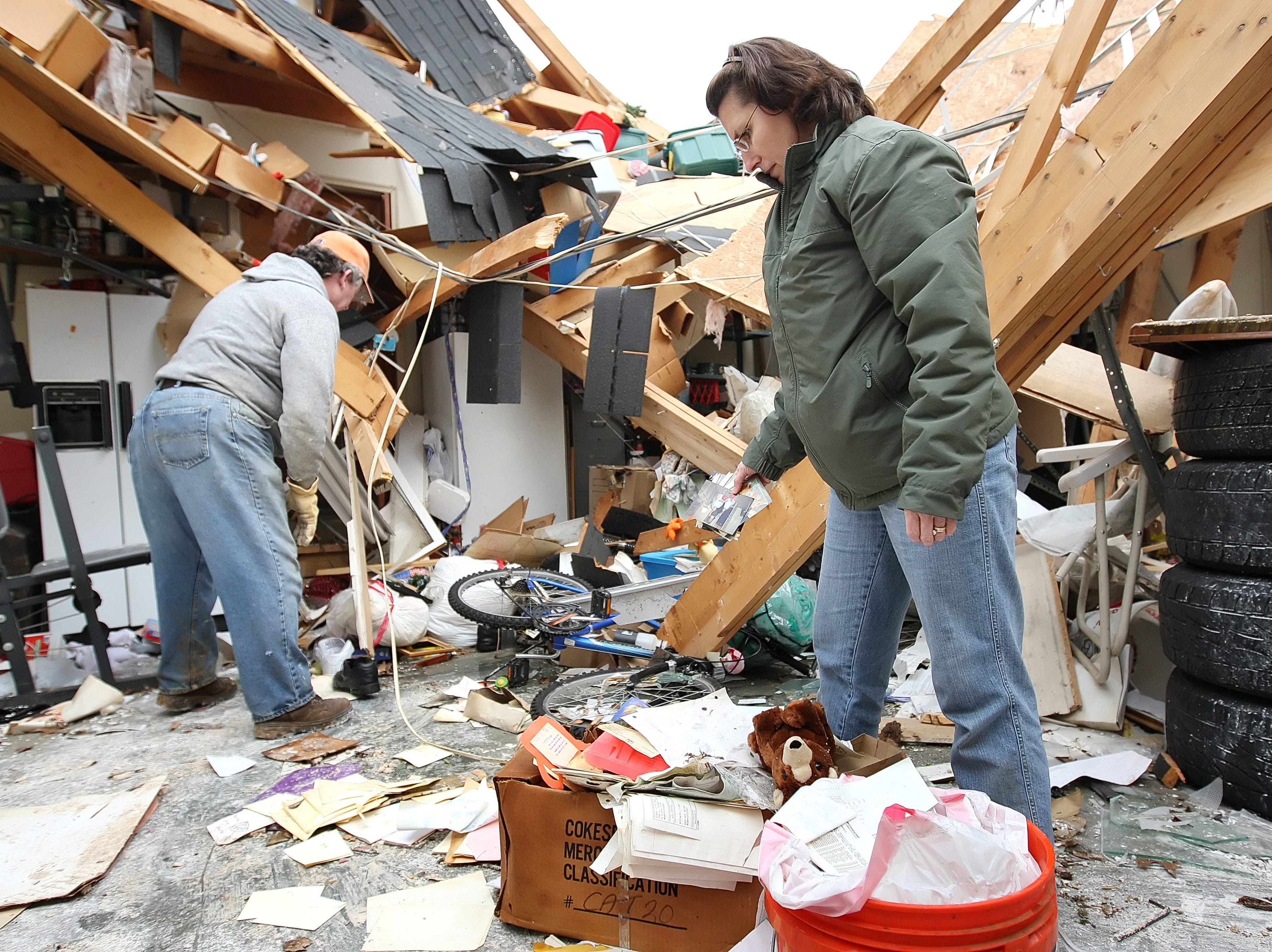 Joanna McClendon, right, looks through a pile of photographs while Dwain Hibdon clears away debris at a home in the Blackman Community which was badly damaged by a tornado in Murfreesboro, Tennessee on Saturday April 11, 2009. (Josh Anderson for The Tennessean)