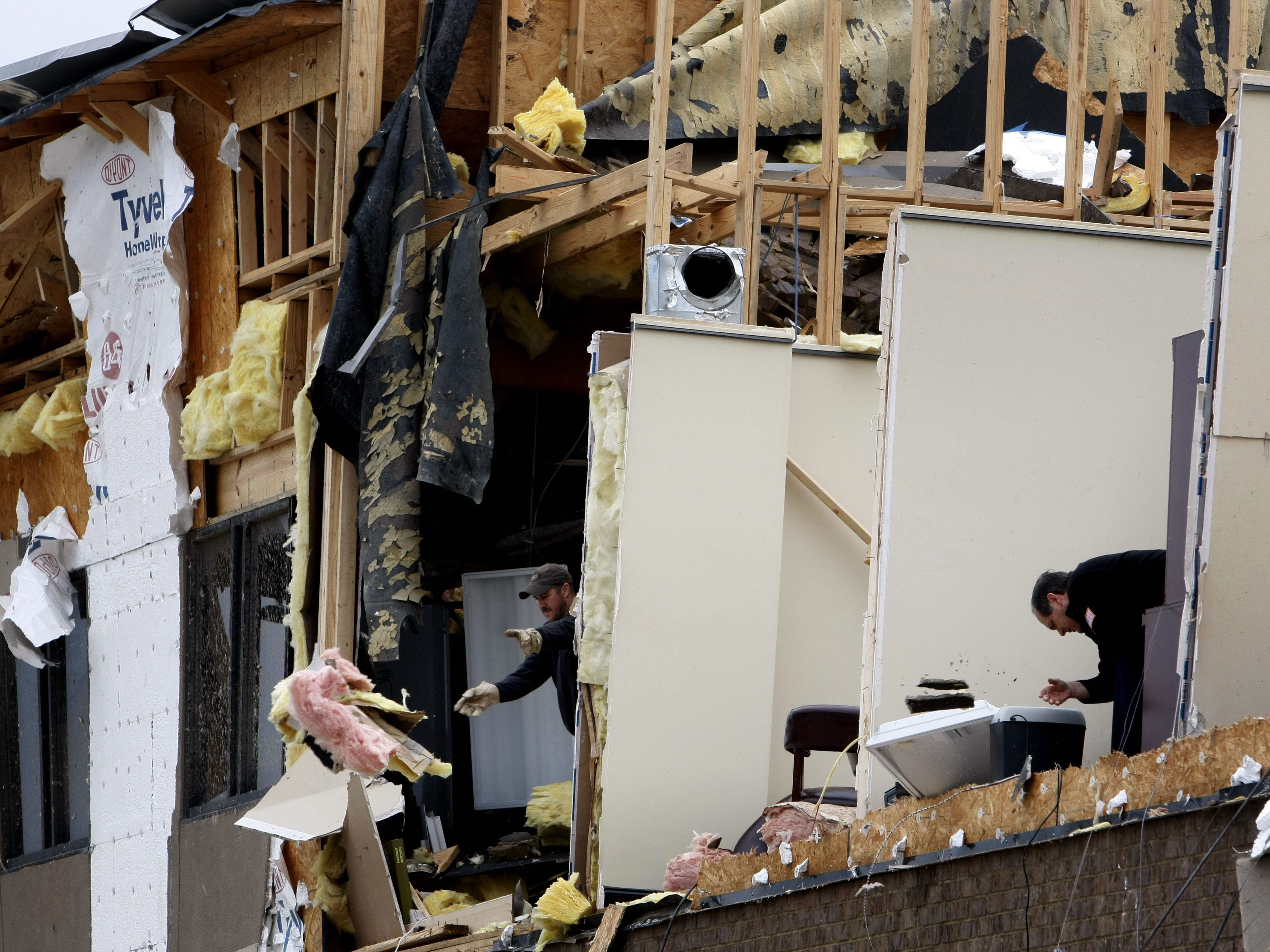 Workers clean the second floor of an office building a day after a tornado roared through Murfreesboro.