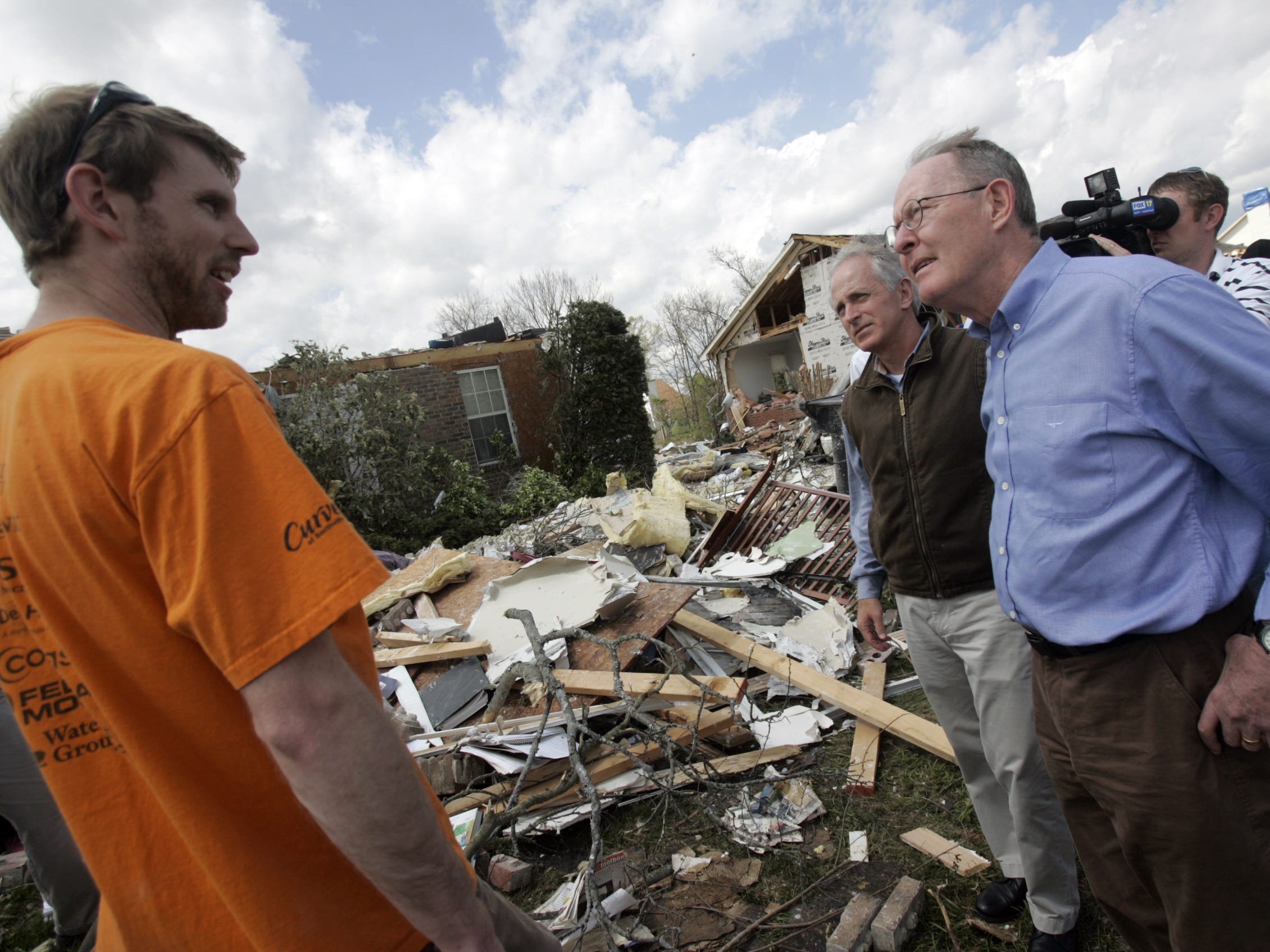 DNJ photo by Aaron Thompson Philip Smith, left, talks with Senators Bob Corker, center, and Lamar Alexander as they tour some of the tornado damage in the Haynes Drive area.