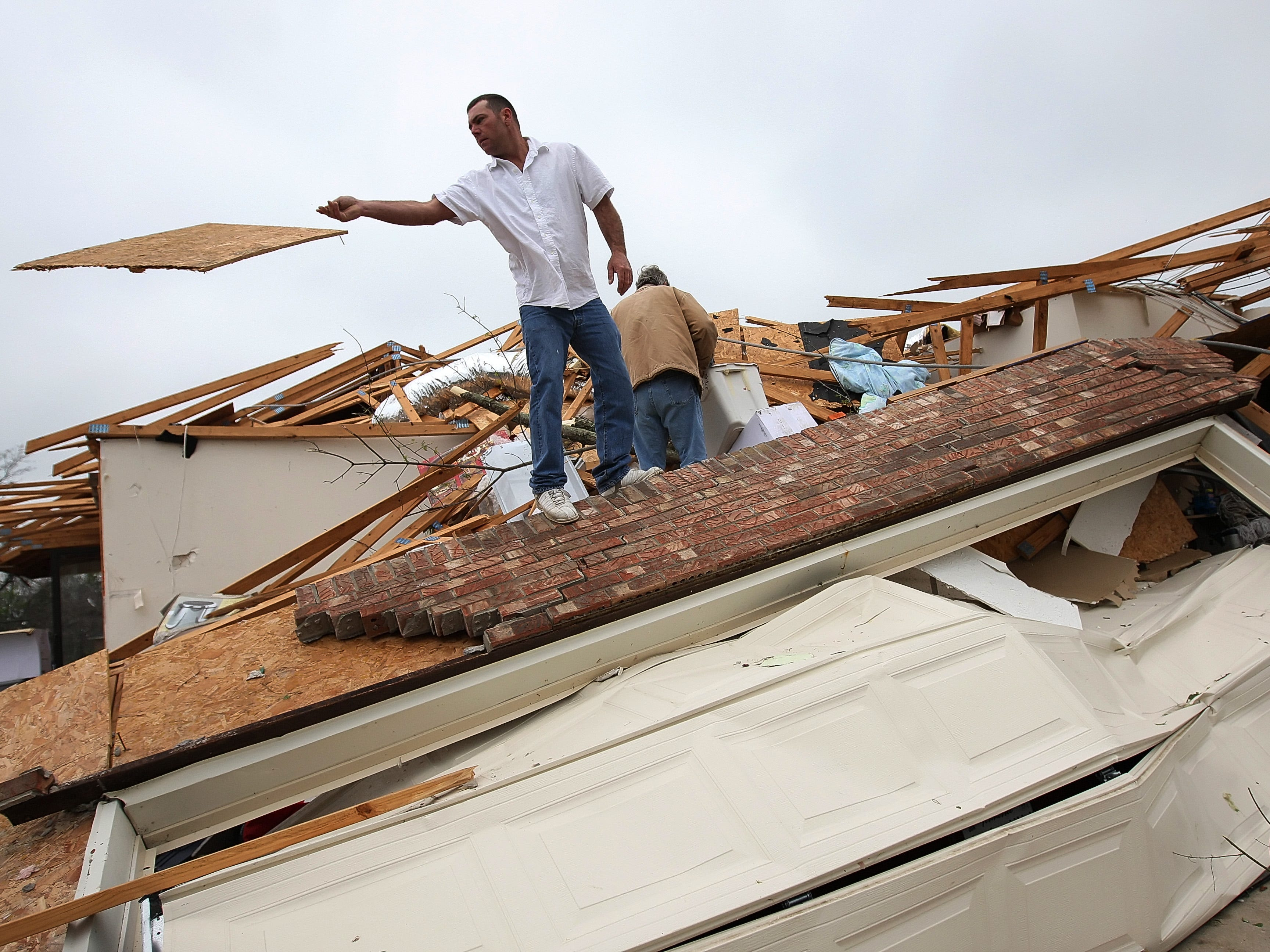 Rick Laster helps to clean up the home of Dave Norwood, not pictured, after Norwoods home was badly damaged in the tornado in Murfreesboro, Tennessee on Saturday April 11, 2009. (Josh Anderson for The Tennessean)