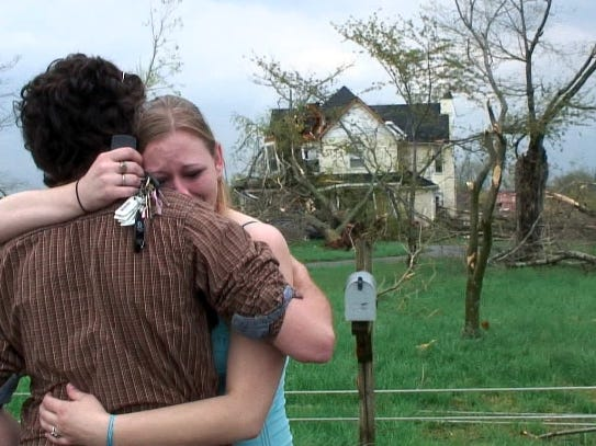 Carrie Warren embraces her boyfriend in front of her house which was destroyed by a tornado Friday, April 10, 2009.