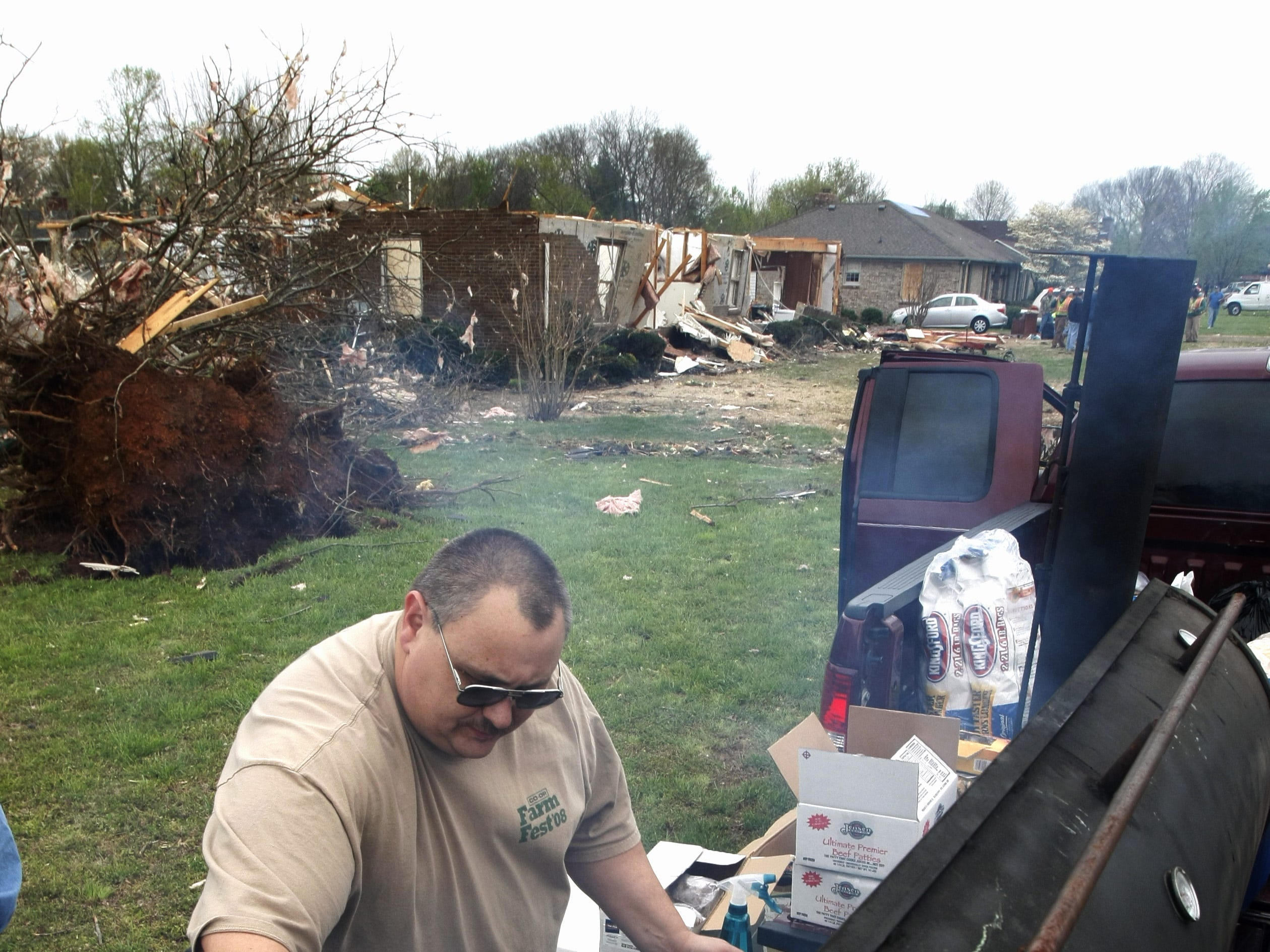 """Brad Campbell of Trinity United Methodist grills bugers and hotdogs to give out to families and workers that were trying to clean up a day after a tornado roared through Murfreesboro. """"We had planned to have this at our Easter Egg Hunt Campbell said,  but decided this would be better."""""""